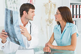 Male doctor explaining spine x-ray to female patient