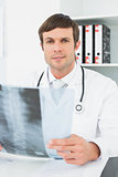 Doctor with x-ray picture of spine in the medical office