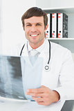 Smiling doctor with x-ray picture of spine in the medical office