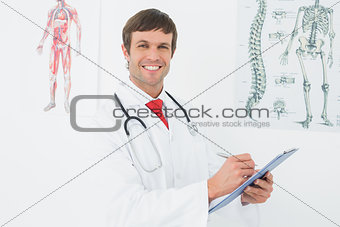 Male doctor holding clipboard in the medical office