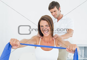 Male therapist assisting young woman with exercises