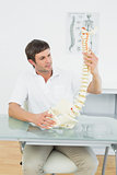 Male doctor holding skeleton model