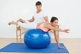 Physical therapist assisting young woman with yoga ball