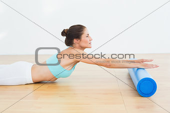 Toned woman doing stretching exercise in fitness studio