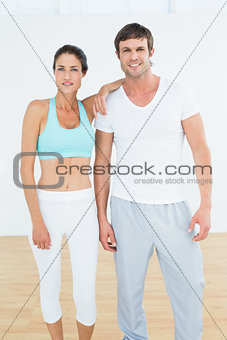 Fit young couple standing in fitness studio