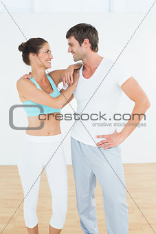 Fit cheerful couple in fitness studio