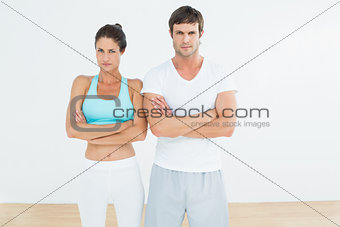 Fit young couple with arms crossed in fitness studio