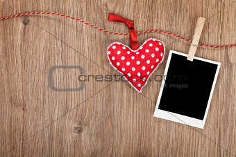Blank instant photo and red heart hanging on the clothesline