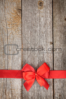 Wooden background with red bow and ribbon