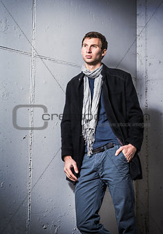 Portrait of handsome young man wearing jeans and coat