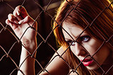 Closeup portrait of beautiful young girl behind metallic grid