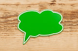 green speech bubble on wood background