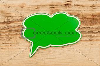 green speech bubble on wood background