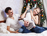 Young family with a baby having fun on bed at home with Christmas tree in the background