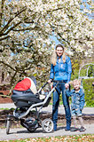 mother and her daughter with a pram on spring walk