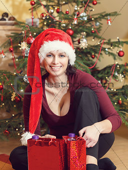 Beautiful middle age woman in santa hat sitting near the Christmas tree