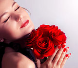 Beautiful female holding red roses bouquet