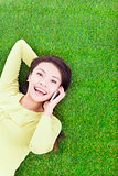 smiling young woman lying with cell phone on green meadow