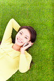 Woman smiling happily on a phone while lying grassland
