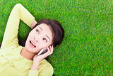 smiling young woman listening with cell phone on grassland