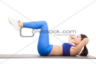 Fit blonde doing pilates core exercise in studio