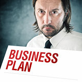 Businessman holding poster with business plan printed title