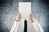 Businessman holding blank paper in front of his face