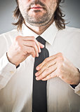 Businessman tying necktie