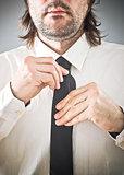Businessman tying necktie