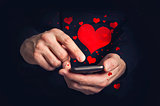 Man typing love text messages on a smartphone for Valentine's da