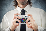 Businessman taking photo with retro style camera