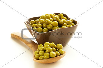 canned green peas in a wooden spoon