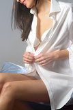 Young woman unbuttoning her shirt