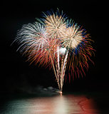 Fireworks display over sea with reflections in water
