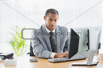 Serious businessman using computer at office