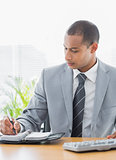 Businessman writing in diary at office desk