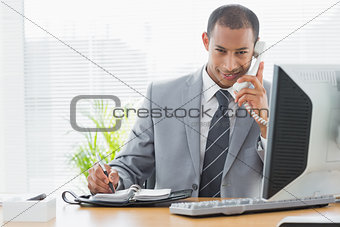 Smiling businessman using computer and phone at office