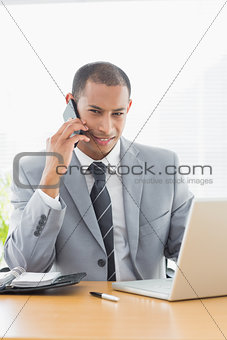 Smiling businessman using laptop and cellphone