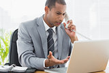 Concentrated businessman using laptop and phone
