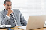 Smiling businessman looking at laptop in office