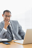 Confident businessman with laptop at office desk