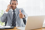 Businessman gesturing thumbs up while on call at office desk