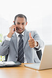 Smiling businessman gesturing thumbs up while on call