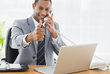Businessman gesturing thumbs up while on call at desk