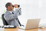 Businessman looking through binoculars at office desk