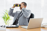 Businessman looking through binoculars at desk