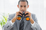 Portrait of a confident businessman with binoculars