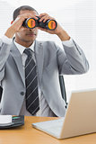 Businessman with binoculars in front of laptop at office