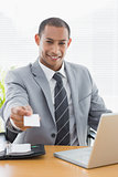 Well dressed man handing business card in front of laptop at office