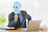 Businessman holding sad smiley faced balloon at office